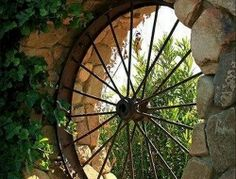 Have you ever thought of using an old wagon wheel for a window? oh this is just awesome ...