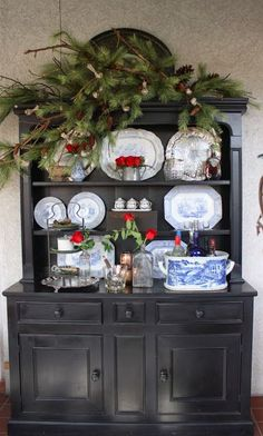 Black hutch makes a stunning backdrop for blue and white dishes, red flowers and holiday greens.