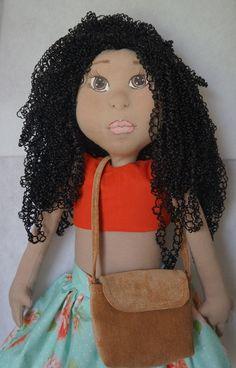 Boneca de pano com rosto modelado  Linda, morena com cabelo estilo afro,  vestida com mini saia e mini blusa de algodão.  Com bolsinha de veludo cotelê  Medindo 75 cm em pé