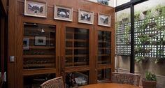 Área externa. Uma varanda foi fechada para ambientar uma adega de madeira e com portas de vidro planjeadas pela La Caves em Ipanema, no Rio Foto: Adriana Lorete / Agência O Globo