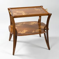 """A French Art Nouveau two-tier table by Louis Majorelle, featuring fruitwood marquetry in a floral design depicting orchids. Pictured in The Paris Salons 1895-1914, Volume III: Furniture, by Alastair Duncan, Antique Collectors' Club Publishers, page 382, and described as """"side table, Exposition Universelle 1900"""". Artist: Majorelle Circa: 1900"""
