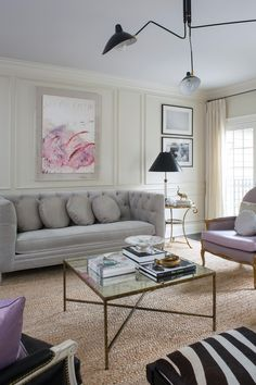 Chic and feminine, this living room features plenty of space to sit and relax. A gray tufted sofa, a pair of lavender armchairs and zebra upholstered stools surround a square coffee table topped with books and personal treasures.