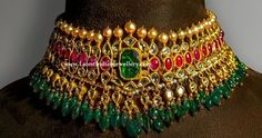 This glorious Polki Ruby Choker necklace from Sayar Jewellery Chennai is the epitome of ethnic glory. A traditional jewel and a must-have in any brides trousseau. This necklace is fashioned with Emerald drops hangings and south sea Pearl's on the top. Gold Temple Jewellery, India Jewelry, Gems Jewelry, Bridal Jewelry, Silver Jewellery, Jewelery, Antique Jewellery Designs, Gold Jewellery Design, South Indian Jewellery
