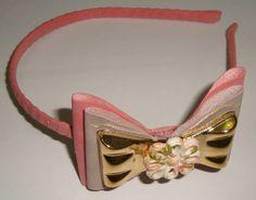 Tiara nas em duas cores: rosa  e rosa chá, com laço dourado e flor em acrílico revestida com material couro ou courino.Peça única R$ 10,00