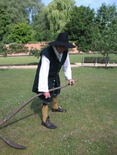 Georgian gardener cutting the lawn with an English scythe. The bent snathe (handle) keeps the blade flat on the grass for a good finish.