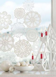 Na parapecie ustaw biały świecznik z czerwonymi świecami, obok połóż kilka białych i srebrnych bombek, a przy pomocy taśmy dwustronnie klejącej przymocuj do szyby koronkowe serwetki. Białe kokosowe pralinki Raffaello mogą imitować śnieżne kule.