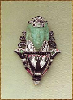 """Broche """"dieu sur une fleur de lotus"""" Atelier Cartier - vers 1925 faience, brillants, émeraudes, rubis, onyx H : 5,5 cm L : 3 cm Collection Cartier Genève"""