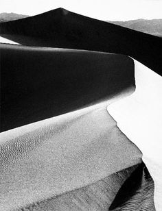 1948 Sand Dune, Sunrise, Death Valley, California [sharp sinuous crest on dune with dark shadows at left, dark peak and mountains beyond] by Ansel Adams 84.92.149