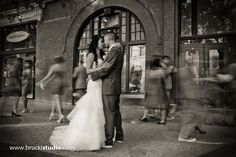 Filipino wedding photography in Winnipeg by Vancouver wedding photographer Trevor Brucki.  Long shutter speed to create motion.  Bride & Groom with wedding party (entourage).  Black and white classic images.  Exchange district, downtown Winnipeg, Manitoba.