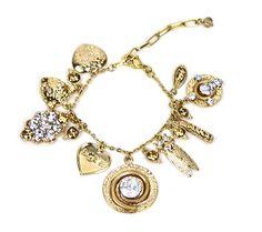 Pulseira Étnica folheado a ouro, no tom envelhecido com berloques variados e detalhes em cristais. Entre os pingentes encontra-se face de pantera, coração, besouro, cacho de cristais e outros.