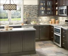 Groutable vinyl tile floor, dark base cabinets, white countertop, glass tile backsplash, and glass front upper cabinets.