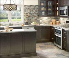 Groutable vinyl tile floor, dark base cabinets, white countertop, glass tile backsplash, and glass front upper cabinets.