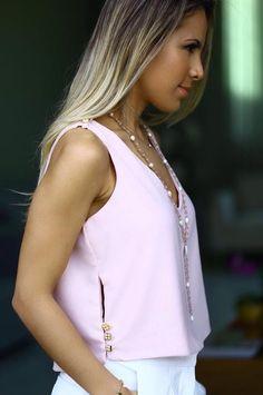 Blusa rosa sin mangas. Detalle de los botones en los laterales.
