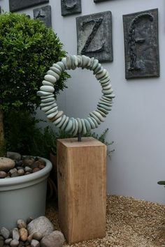 japanese green sandstone pebbles, drilled and threaded onto galvanised steel armature, mounted on french oak base. dimensions 400mm diameter, 940mm tall including wood.