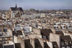 View of rooftops, chimneys + landmarks from the Marais in Paris. Photo by Rita Crane.