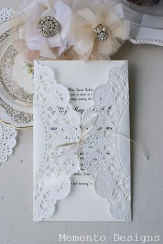 Easy and simple wedding invitations. Doily folded over the invitation and tied together with a small ribbon.
