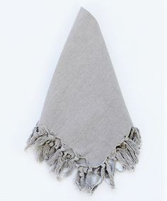 Elephant Grey Napkin with Fringe - Create a nuanced table setting with layers of detailed textiles like the Elephant Grey Napkin with Fringe. Edged in upscale tassels, this soft cotton napkin offers more dimension than a simple square and provides a bouquet of lush details when pulled through a napkin ring. Layer this neutral table napkin with a colorful organza companion or a crisp, striped linen runner for a thoughtful setting.