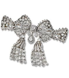 Important Diamond corsage ornament, Cartier, 1907. Designed as an openwork tied ribbon bow set throughout with circular- and rose-cut Diamonds, supporting two detachable tassels set with similar stones, mounted in Gold and Silver, may be worn as a brooch, a pendant or a choker, both tassels to be worn as ear-clips, signed Cartier Paris, French assay marks, in a later fitted case, accompanied by a screwdriver and fittings for choker.