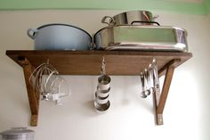 Great idea for kitchen storage - put hooks underneath shelves!
