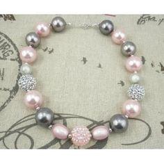Perfecto accesorio para conseguir la imagen más chic y elegante de una bebé. Compuesto de imitaciones de gruesas perlas y abalorios swarovsky en suaves tonalidades grises y rosas. Largo aproximado: entre 40 y 50 cm.