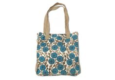 Stroll the farmer's market in style with this beauty on your shoulder. Hand-woven in a cotton fabric with a blue-floral print and jute handles, this tote is the perfect size for transporting groceries, beach towels and other essentials.