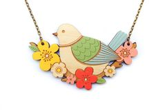 """This exquisite necklace is part of the 'In the Trees' collection by Layla Amber, featuring a stunning range of birds and flowers.Layla Amber designs and hand makes her beautiful jewellery pieces in her Southwold, Suffolk studio.The Blue Tit and Flowers necklace is like a mini work of art. It is made from laser cut birch wood and is carefully hand painted in delicate, Spring like colours. It hangs from an 18"""" antique gold style chain and is simply stunning pair..."""