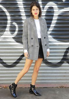 Leandra Medine from Man Repeller sports a simple look with an oversized blazer, leather mini skirt and plain white tee, styled with leather ankle boots.