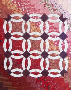 Double Wedding Ring Quilt Wall Hanging by Patch Forest.  I think the maker appliqued the rings and conerstones onto a pieced background.  Very pretty.etsy