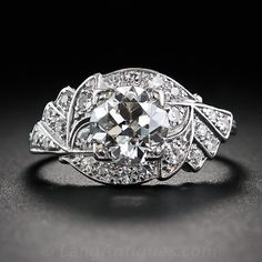 This singular and sensational sparkler, from the 1930s, radiates front and center with a gorgeous 1.20 carat European-cut diamond. The center stone beams atop an especially graceful Art Deco setting designed and rendered in a highly stylized, mirror-image wing motif glistening with an array of bright single-cut diamonds. An original vintage dream ring.