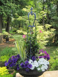 Crowned planter with petunias, iris, and mandevilla
