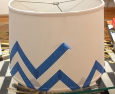 Take a simple lamp, add tape, spray paint, then remove the tape to reveal the pattern