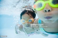 Stock Photo : Hispanic girls swimming underwater in pool