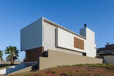 Casa com fachada moderna, brise de madeira, textura de cimento. Casa RA Arquitetura Contemporânea em Campo Grande por MOB Arquitetos