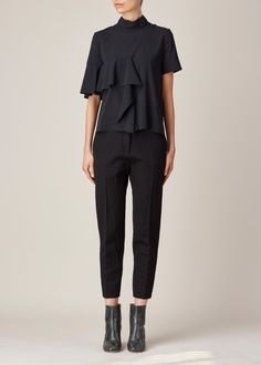 Short-sleeved mock neck ruffle front top in black stretch silk georgette. Draped ruffle embellishment at front. Hidden zip closure at back of neck. Dry clean.