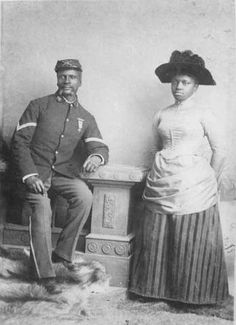 "Studio portrait of African American officer and woman, Company D, 25th United States Infantry Regiment ""Buffalo Soldiers"", Fort Custer, Mont..."