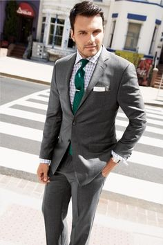 A great combination of color and pattern! Here the emerald green polka dot tie is paired with a window-pane check shirt, and stone gray suit...