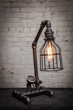 This is a handmade desk lamp made from steel pipe. It has an integrated bulb and built-in on/off switch. The bulb is housed in a steel cage and the