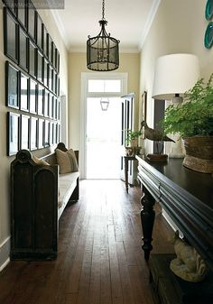 Lantern in this narrow entrance hallway with dramatic framed prints on one side and hall table with lamp on the opposite - a very chic entrance