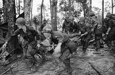 18 May 1969, A Shau Valley, South Vietnam: A quartet of U.S. 101st Air Division troopers keep low as  they rush a stretcher-borne wounded comrade to a medical aid station  during the battle for Hamburger Hill.  New fighting erupted about the  controversial hill on May 23.