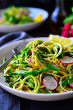 This spring vegetable zoodle pasta with garlicy lemon sauce is light and fresh and the perfect way to take advantage of the season's vegetables. Lightly blanched asparagus and snow peas are tossed with zucchini noodles and whole wheat pasta and topped with crispy radishes. A quick and easy recipe for a busy weeknight dinner. #wholewheatpastarecipenoodles #freshwholewheatpastarecipe