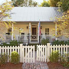 X Marks the Spot - During warm months, a wooden screen door with an X-motif is the only barrier between the house and the gorgeous front porch. A handsome picket fence and classic brick path create a warm invitation to the home's entry. Front Door With Screen, Wooden Screen Door, Screen Doors, Farmhouse Front, Farmhouse Style, Modern Farmhouse, Front Porch Railings, Modern Fence Design, Brick Path