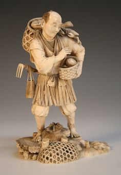 A Japanese ivory okimono figure of a fisherman, Meiji period, finely carved bearing two fish laden baskets, a crab upon his shoulder, a sack and nets at his feet, signed to red lacquer seal mark to base, height approx 16cm.