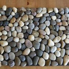 How to Make a Pebble Stone Mat.  The link to this is squirly, but basically its a plain rubber welcome mat, river stones and contact adhesive. Author got everything at the dollar store. Looks like it would take at least 6 bags of rocks. Still, could do this one for under 10 bucks