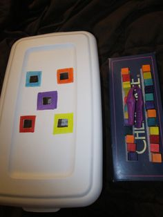 Task Box- Student uses the tweezers to take the cubes off the velcro (on the shoe box lid) and push them through the lid of the plastic box