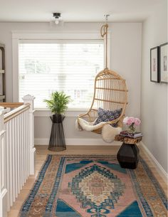 hanging rattan + turkish rug warms space atop stair landing.