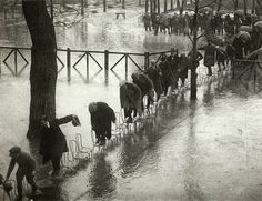 24 Rare Historical Photos That Will Leave You Speechless - People in Paris avoid getting wet in the flood by stepping on a series of chairs in 1924.