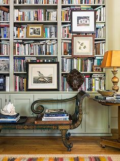 A soft green-gray serves as a sophisticated background color of choice in this eclectic library design.