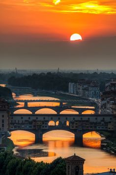 Florence, Italy. Spectacular photography! The shape of the sun setting has been captured in the arches of the bridges!