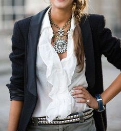Black blazer with ruffle shirt gray pants and big necklace.