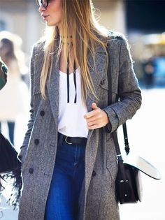 A thin ribbon choker is paired with a v-neck tee, gray coat, jeans, and a saddle bag